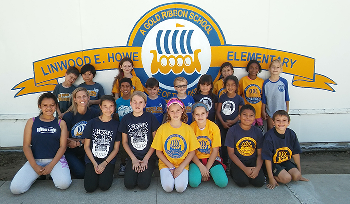 Dr. Indelicato, with kindergarteners to fifth graders, in front of the school's new Gold Ribbon mural. Photo, Jasmine-Joy Cason, City Year