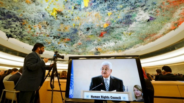Palestinian Authority President Mahmud Abbas is seen on a TV screen while speaking during a meeting of the United Nations Human Rights Council on Feb. 27, in Geneva. (AFP/Fabrice Coffrini)